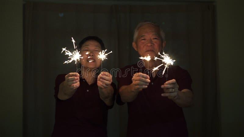 Азиатские старшие пары играя бенгальские огни, шутиху огня вечером Концепция празднуя жизнь стоковое фото rf