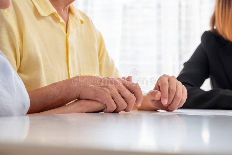 Азиатские старшие пары проводя руку с халатным и дискуссию с финансовым советником о документе налога и выхода на пенсию дома t стоковое фото