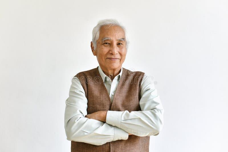 Азиатские старший старик, уверенный и усмехаться престарелый со сложенным жестом оружий на белой предпосылке стоковая фотография rf
