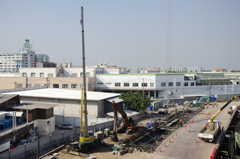 Азиатские тайские работники и здание построителя тяжелой техники работая новое на многоэтажном здании строительной площадки в Бан стоковое изображение