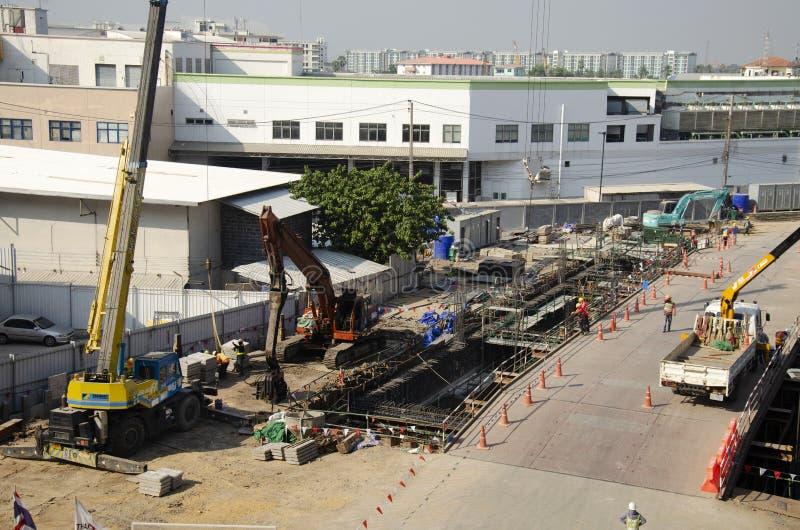 Азиатские тайские работники и здание построителя тяжелой техники работая новое на многоэтажном здании строительной площадки в Бан стоковые изображения rf