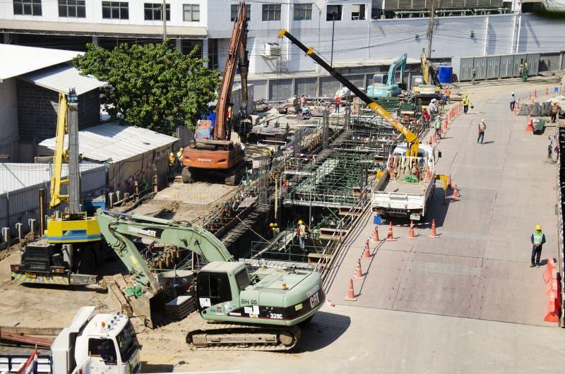 Азиатские тайские работники и здание построителя тяжелой техники работая новое на многоэтажном здании строительной площадки в Бан стоковое изображение rf