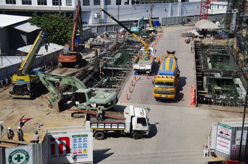 Азиатские тайские работники и здание построителя тяжелой техники работая новое на многоэтажном здании строительной площадки в Бан стоковая фотография rf