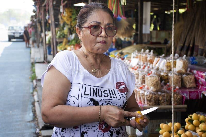 Азиатские тайские старухи испытывают для еды и для покупки ходя по магазинам сливы Мэриан или манго gandaria или сливы на местном стоковая фотография rf