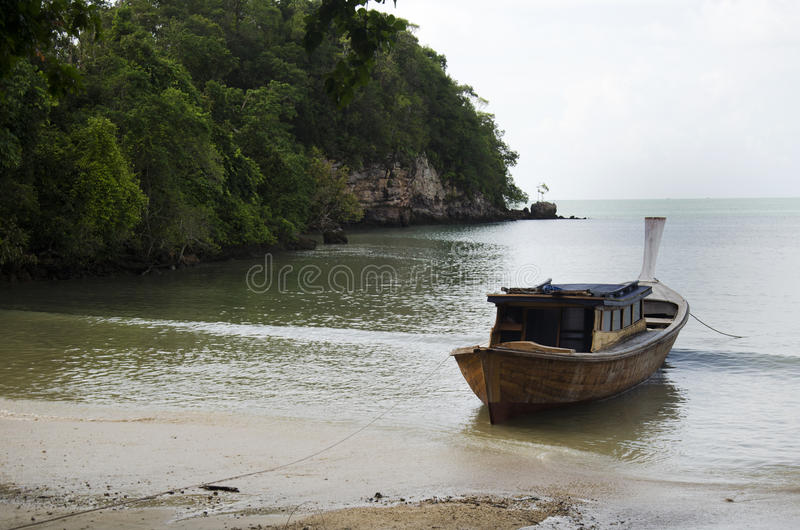 Азиатские тайские люди останавливают деревянную моторную лодку на заливе на пляже внутри стоковые фотографии rf