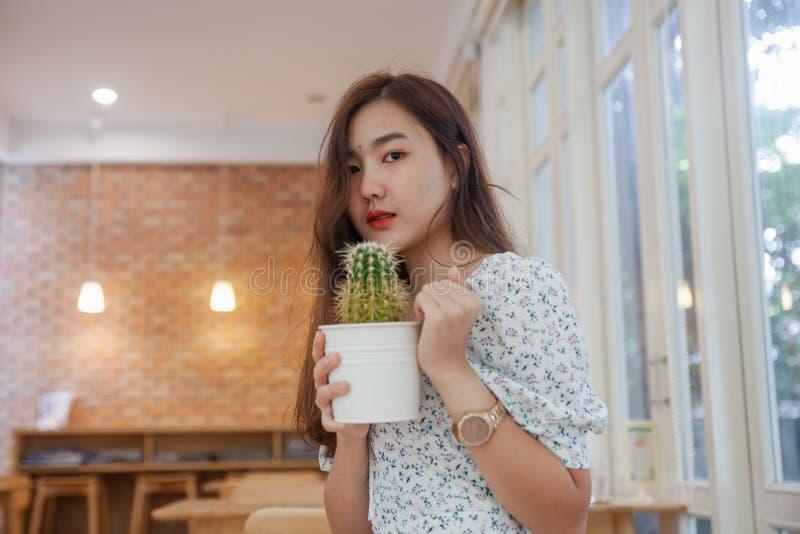 Азиатский бак кактуса удерживания женщины на кафе стоковые изображения rf