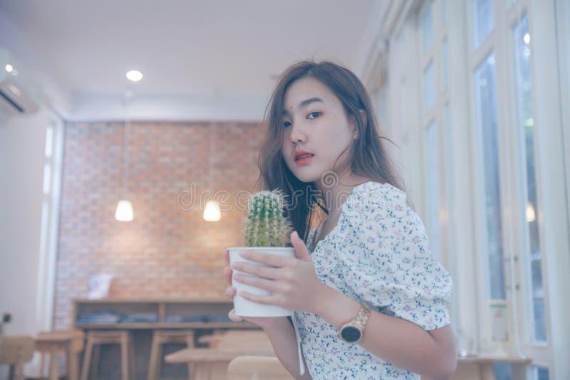Азиатский бак кактуса удерживания женщины на кафе стоковое фото