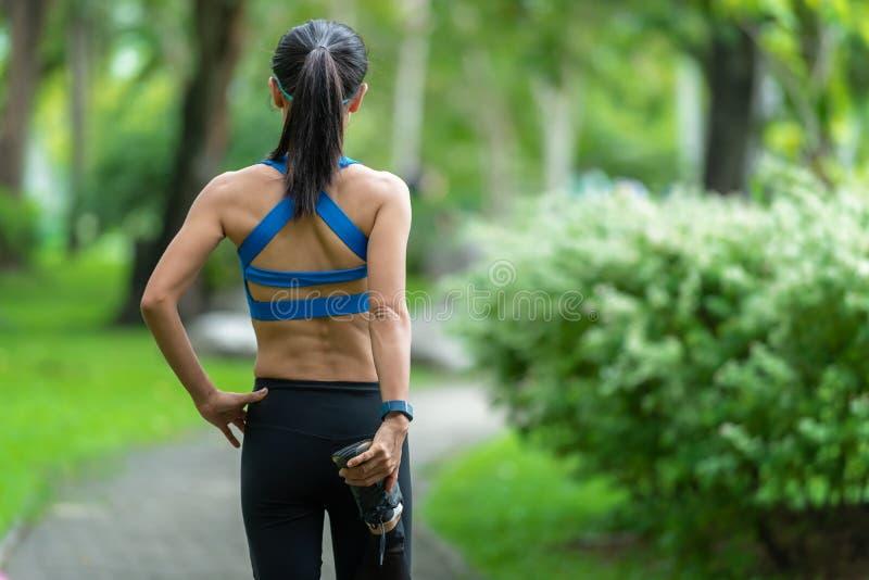 Азиатский бегун женщины фитнеса протягивая ноги перед разминкой бега внешней в парке стоковые фотографии rf