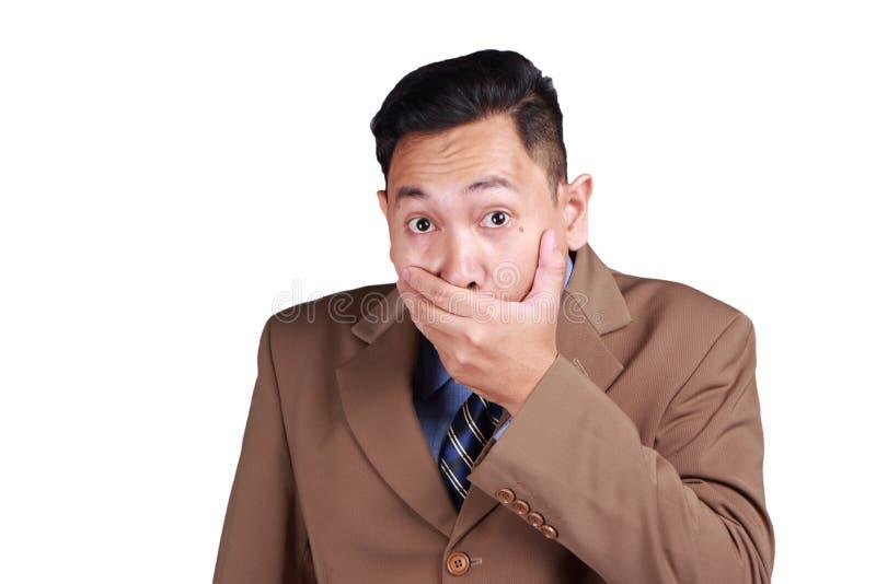 Азиатский бизнесмен закрывая его рот с пальцами стоковое изображение