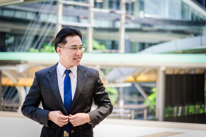 Азиатский бизнесмен имеет застегивать одежды костюма черноты стоковые изображения rf
