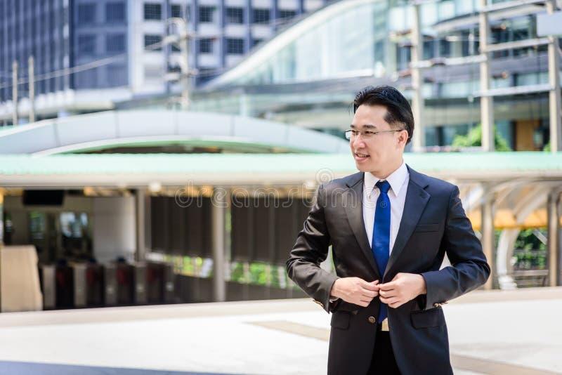 Азиатский бизнесмен имеет застегивать одежды костюма черноты стоковое изображение