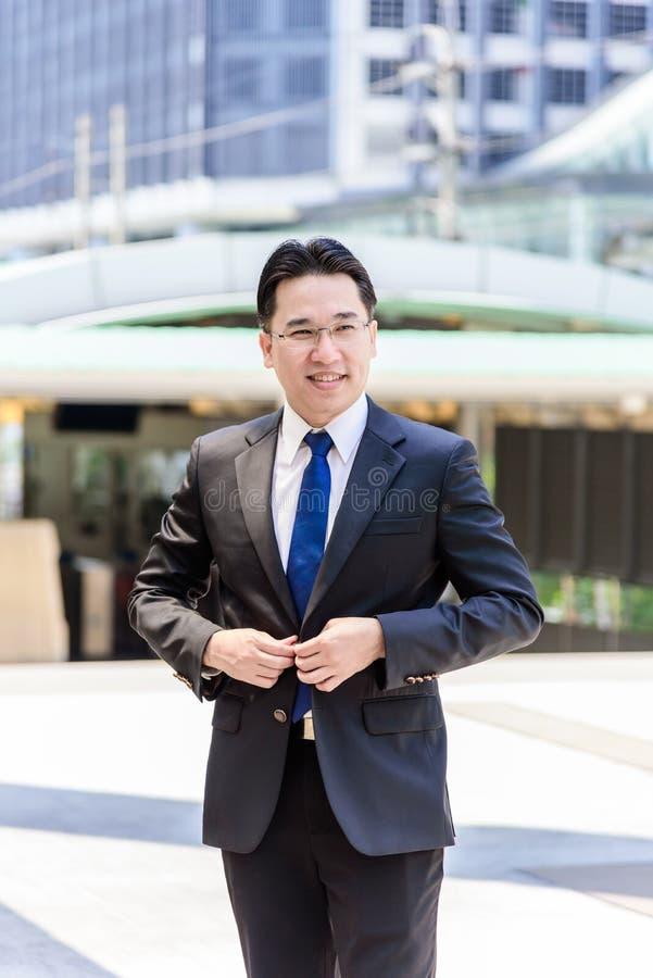 Азиатский бизнесмен имеет застегивать одежды костюма черноты стоковая фотография rf