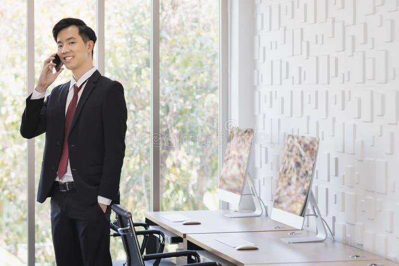 Азиатский бизнесмен используя мобильный телефон в офисе стоковые изображения rf