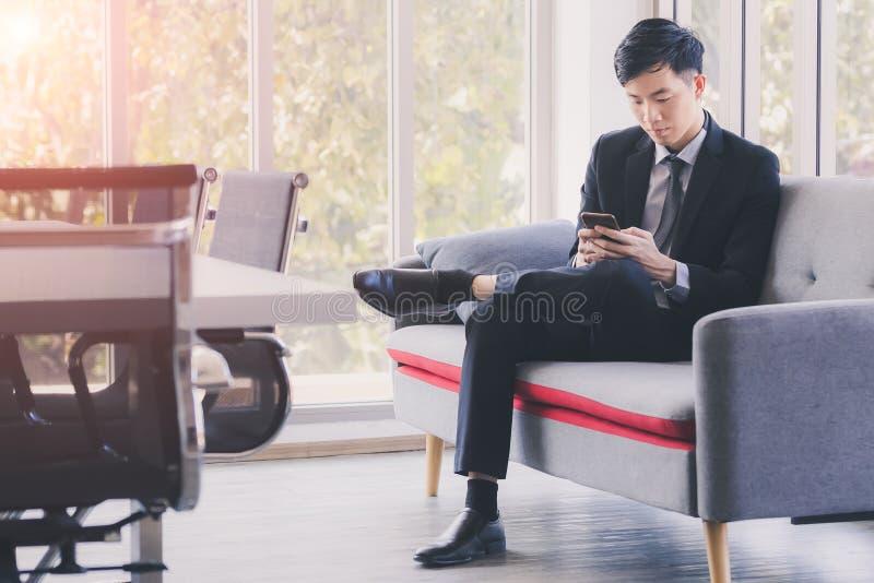 Азиатский бизнесмен используя мобильный телефон в офисе стоковая фотография rf