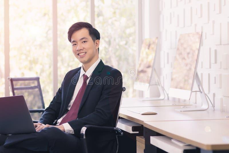 Азиатский бизнесмен используя ноутбук в офисе стоковые фото