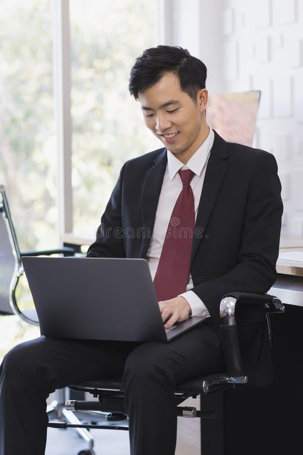 Азиатский бизнесмен используя ноутбук в офисе стоковая фотография