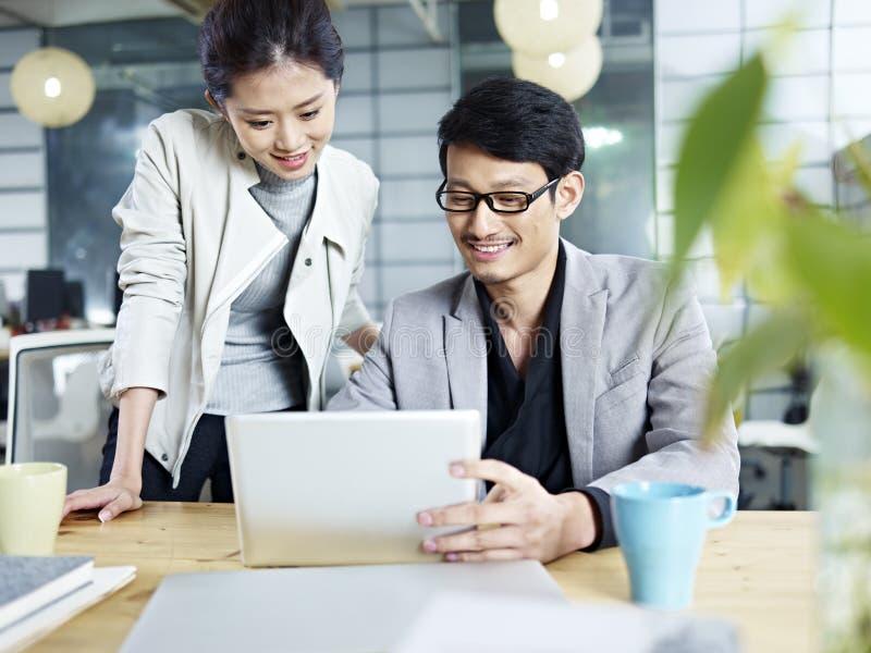 Азиатский бизнесмен и женщина работая совместно в офисе стоковые фотографии rf
