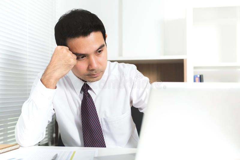 Азиатский бизнесмен получая усиленный на работе стоковое изображение rf