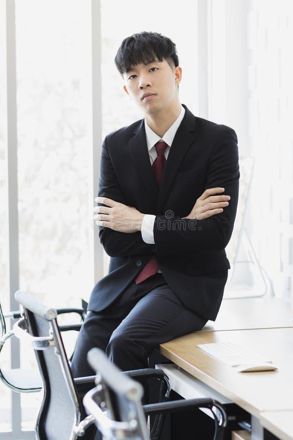 Азиатский бизнесмен сидя и представляя в офисе стоковые фотографии rf