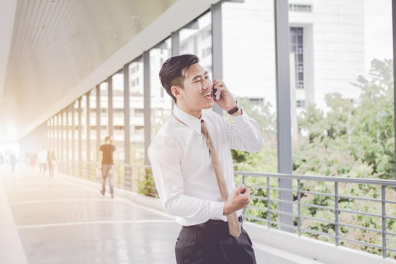 Азиатский бизнесмен усмехаясь телефон звонка говоря и ослабляет, встречи между исполнительными властями между ждать дальше на тро стоковая фотография rf