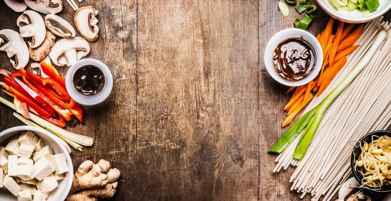 Азиатский вегетарианец варя ингридиенты для фрая stir с тофу, лапшами, овощами и соусами на деревянной деревенской предпосылке, в стоковые изображения