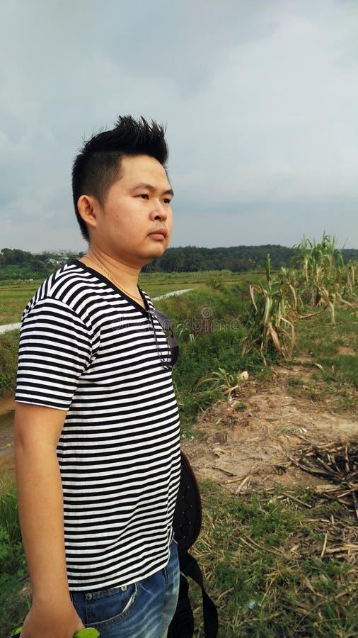 Азиатский взгляд человека на заходе солнца стоковая фотография