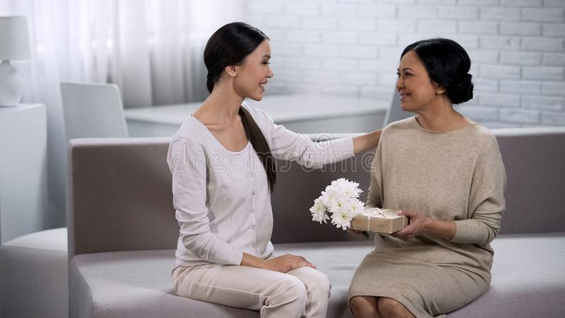 Азиатский давать девушки присутствующий к матери, празднуя годовщину замужества, семья стоковые фото