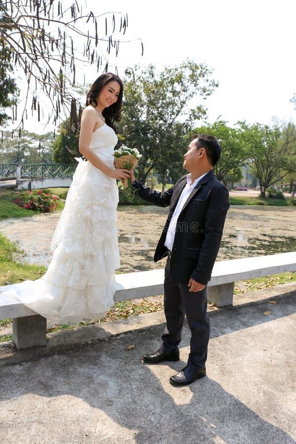 Азиатский жених давая его невесте симпатичный букет стоковое фото