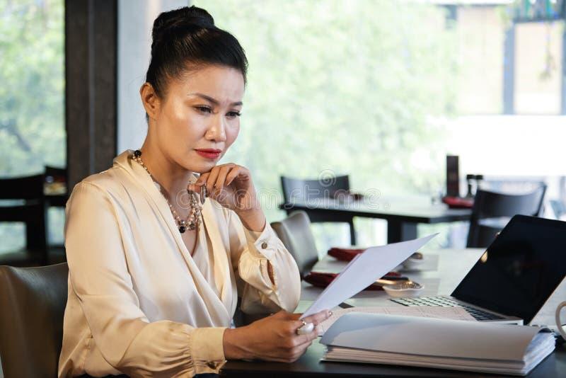 Азиатский женский концентрировать на бумагах дела чтения стоковая фотография rf