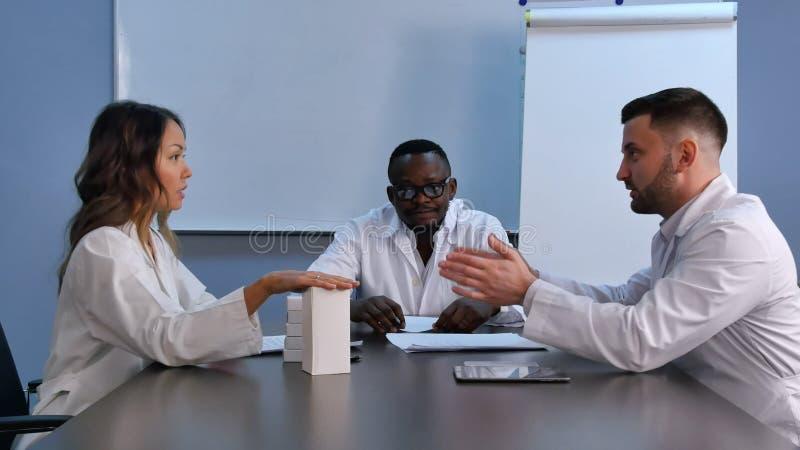 Азиатский женский доктор представляя новые пилюльки к коллегам стоковое изображение rf