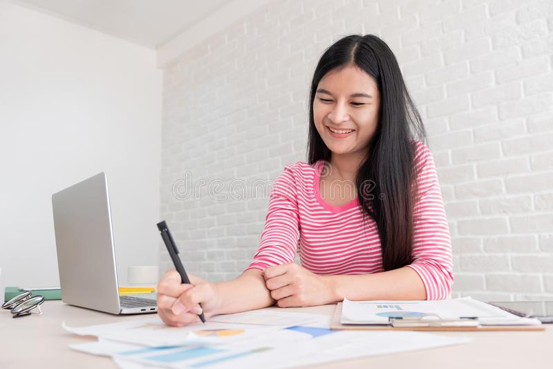 Азиатский женский фрилансер работая на портативном компьютере на таблице на b стоковые фото