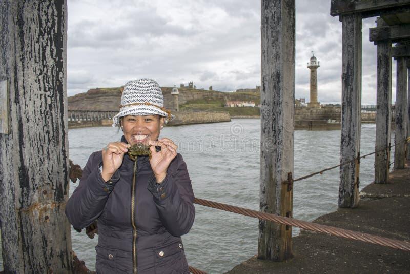 Азиатский женский Crabbing на пристани северном Йоркшире Whitby западной, Engla стоковое фото rf
