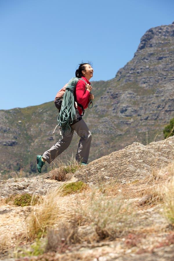 Азиатский женский hiker идя скалой с рюкзаком и взбираясь веревочкой стоковые фото