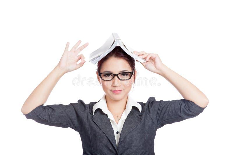 Азиатский знак О'КЕЙ выставки бизнес-леди с книгой на ее голове стоковое фото