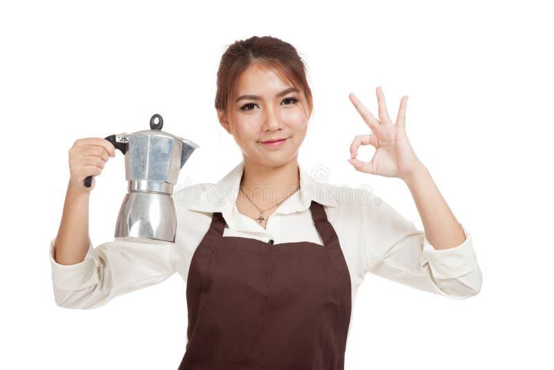 Азиатский знак О'КЕЙ выставки девушки barista с баком Moka кофе стоковые фото