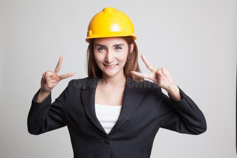 Азиатский знак победы выставки женщины инженера с обеими руками стоковые изображения rf