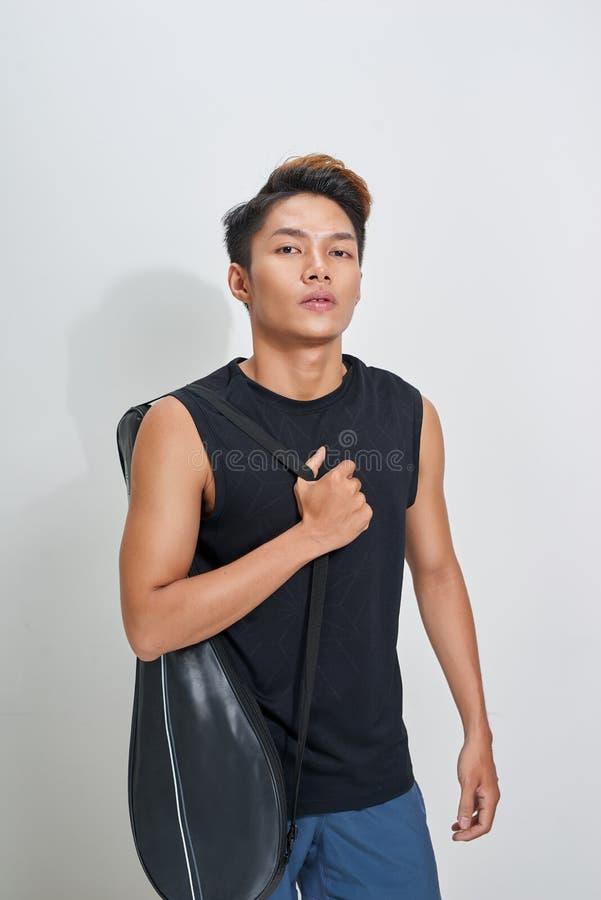Азиатский игрок бадминтона с сумкой на белой предпосылке стоковое изображение rf