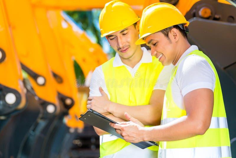 Азиатский инженер обсуждая планы на строительной площадке стоковое фото rf