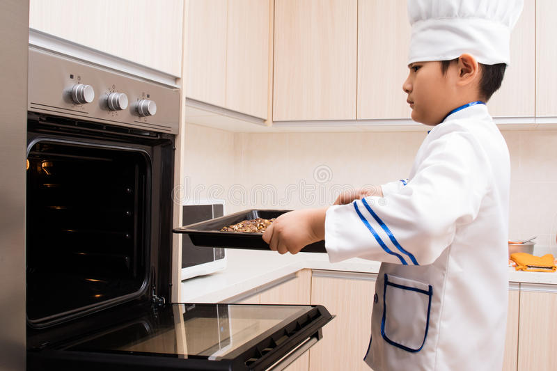 Азиатский китайский мальчик в печеньях выпечки белого шеф-повара равномерных стоковые изображения rf