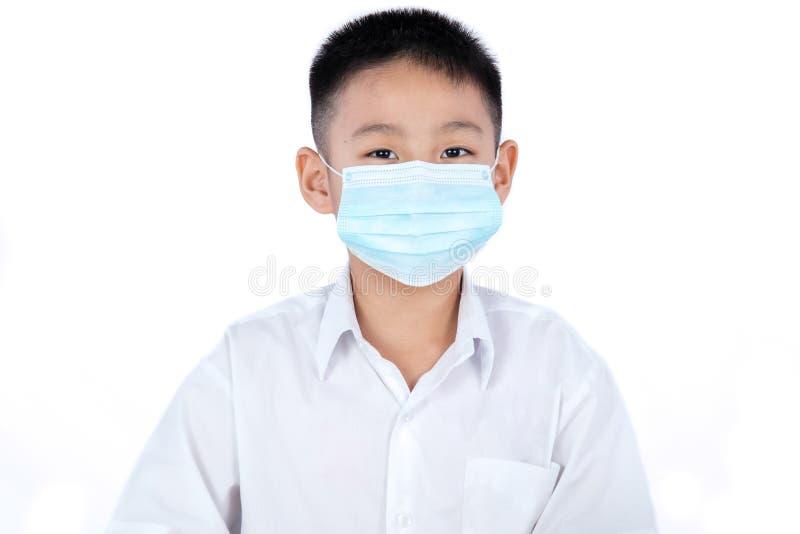 Азиатский китайский мальчик студента в равномерной нося маске стоковая фотография