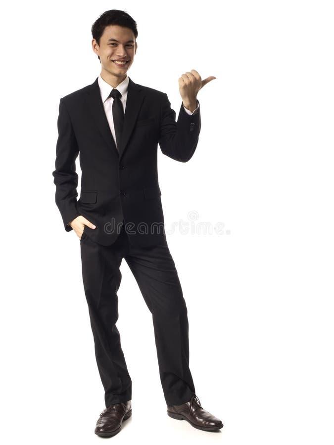 азиатский корпоративный человек над указывать детеныши большого пальца руки стоковая фотография