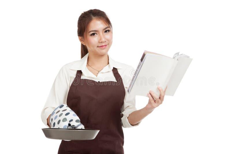 Азиатский красивый кашевар девушки с сковородой прочитал книгу кашевара стоковое фото