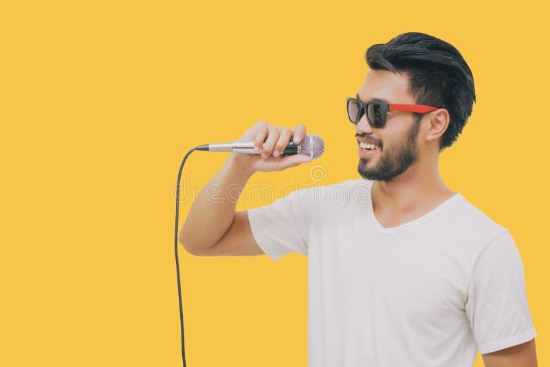 Азиатский красивый человек с усиком, усмехаясь и поя к микрофону на же стоковое фото
