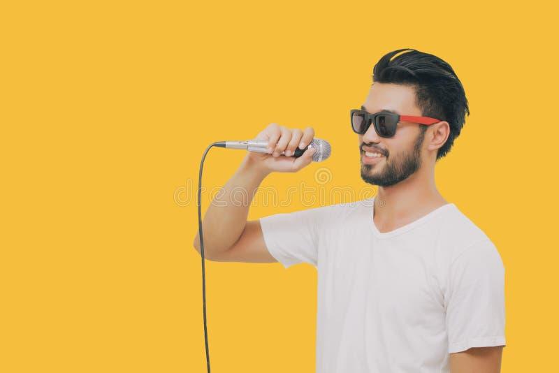 Азиатский красивый человек с усиком, усмехаясь и поя к микрофону на же стоковая фотография