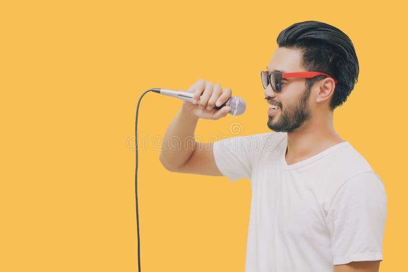 Азиатский красивый человек с усиком, усмехаясь и поя к микрофону изоли стоковые изображения