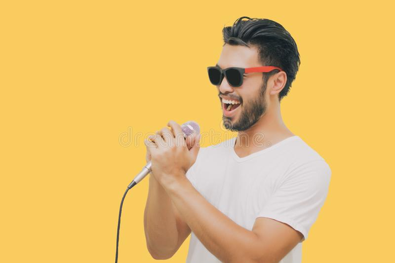 Азиатский красивый человек с усиком, усмехаясь и поя к микрофону изоли стоковое изображение rf