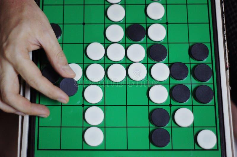 Азиатский круг черноты владением руки человека Othello Reversi на настольной игре стратегии Othello стоковое фото