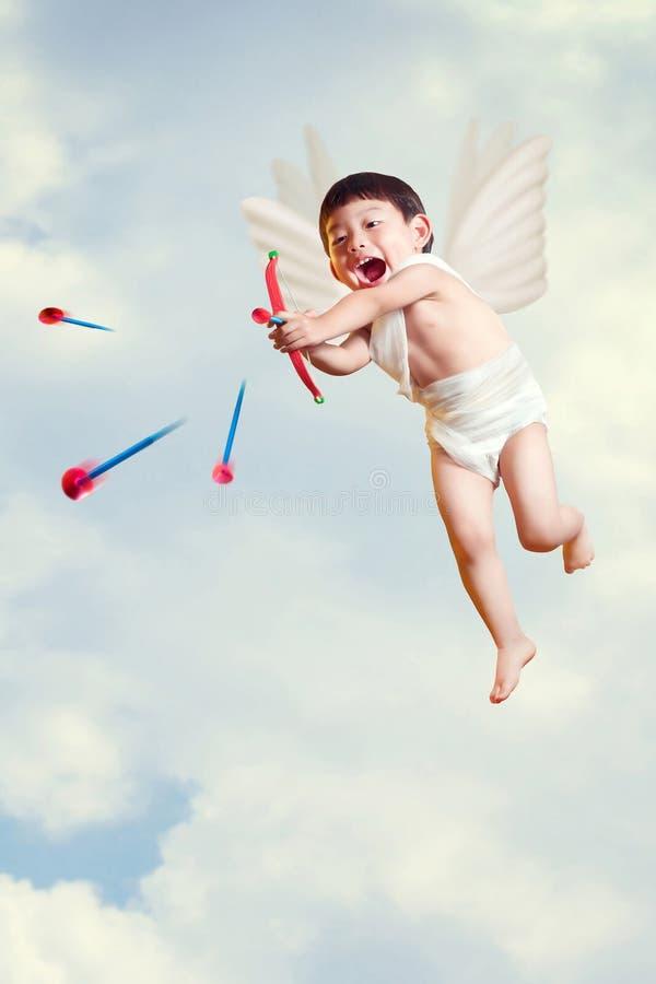 Азиатский купидон мальчика с мухой лука и стрелы в небе стоковые изображения rf