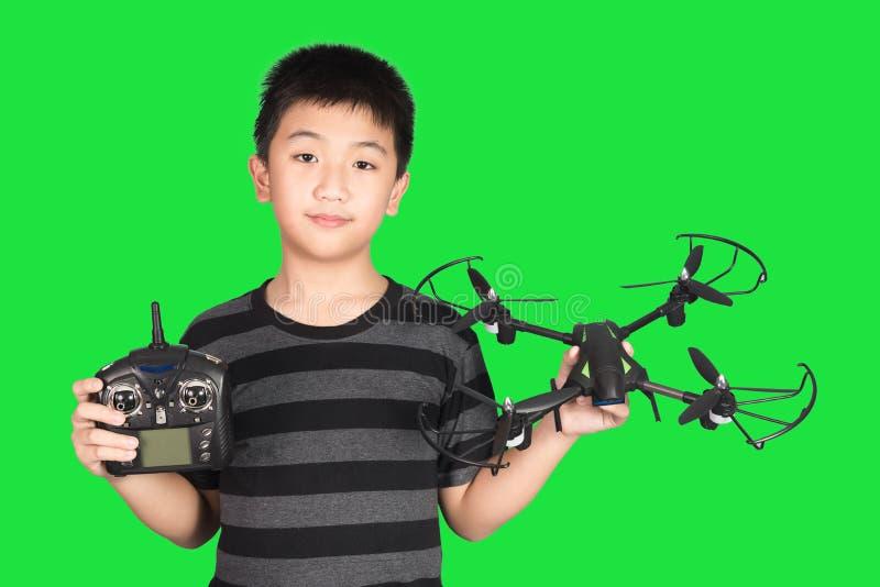 Азиатский мальчик держа дистанционное управление трутня и радио handset для hel стоковое изображение rf