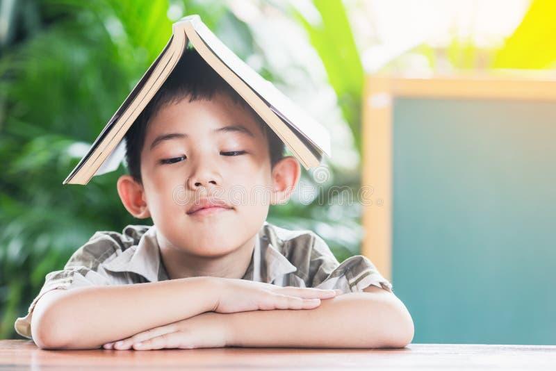 Азиатский мальчик держа книгу на голове стоковые изображения rf